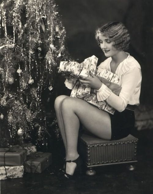 A very young Carole Lombard poses with Christmas gifts.