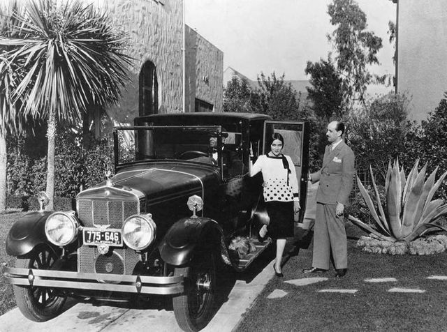Dolores Del Rio about to leave home for the studio in her Franklin. Husband Jaime holds the door for her.