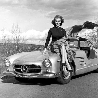 Sophia Loren poses on the hood of the classic gullwing Mercedes-Benz 300 SL. Gullwing