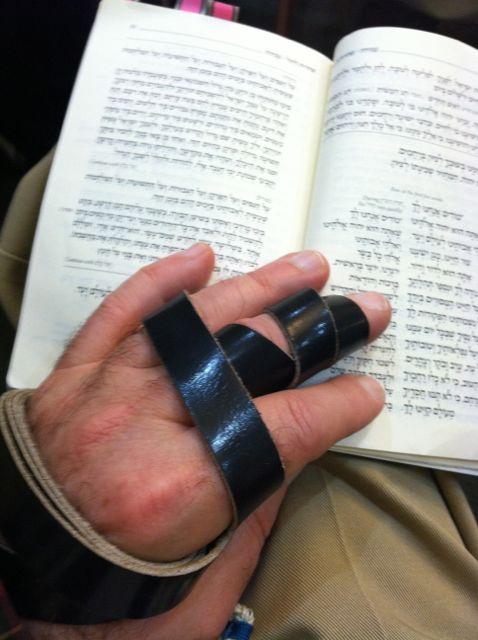 The obligation to put on tefillin, as expounded by the Oral Law, is mentioned four times in the Torah. The arm-tefillin straps are wound first around the forearm seven times, and then three times around the middle finger and around the hand to form the shape of the Hebrew letter of either a shin (ש) according to Ashkenazim, or a dalet (ד) according to Sephardim. This is me, praying in morning minyan. My tradition is Ashkenazi.