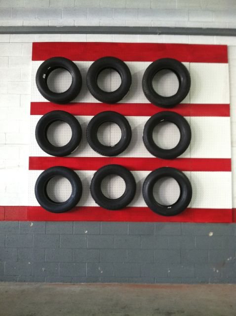 Brought my car into the shop for an oil change and was transfixed by this composition of tires bisected by red bars.