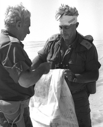 In this Oct. 10, 1973 file photo, Maj. Gen. Ariel Sharon, right, views a map together with Maj. Gen. Haim Bar-Lev in the Sinai desert, during the 1973 Middle East War.