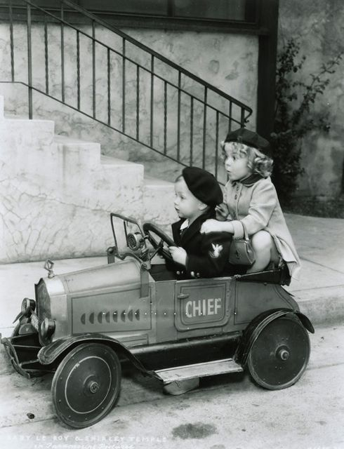 Shirley Temple with Baby LeRoy cruising in a Fire Chief car, early 1930s.