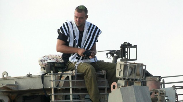 An IDF soldier prays atop an armored bulldozer near the Gaza border.