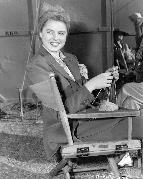 On location for the Hitchcock masterpiece Notorious, Ingrid Bergman looks deeply un-notorious as she knits while waiting to act.