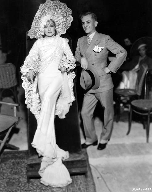 Marlene Dietrich leans on the set of The Devil is a Woman with band leader Manuel L. Quezon.