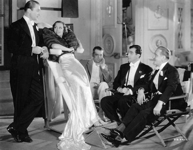 "Brian Aherne, director W.S. Van Dyke, Fred Keating and Frank Morgan pose with Joan Crawford on her resting board during production of ""I Live My Life"" ('35)."
