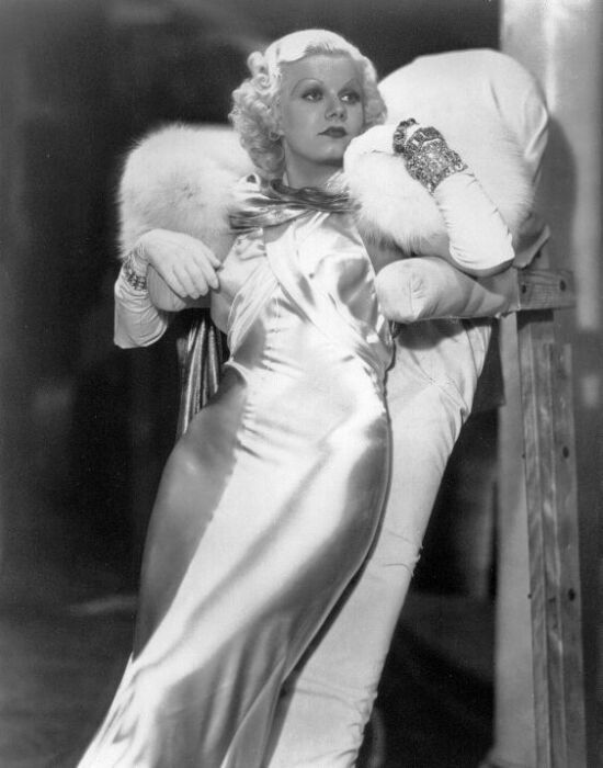 Jean Harlow propped up on a leaning board between scenes for Dinner at Eight ('33). The Adrian designed gown was so tight that Harlow could not sit, nor wear any undergarments.