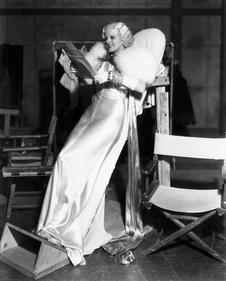 "Jean Harlow propped up on a leaning board between scenes for ""Dinner at Eight"" ('33). The form fitting silk gown designed by Adrian was so tight that Harlow could not sit. In fact, Harlow was sewn into the gown — sans underwear."