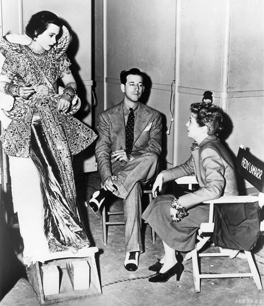 Hedy Lamarr leans as Janet Gaynor visits husband Adrian on the set of Lady of the Tropics.