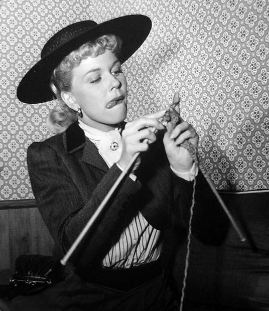 "Doris Day concentrates very hard on her stitches on the set of ""By the Light of the Silvery Moon,"" 1953."