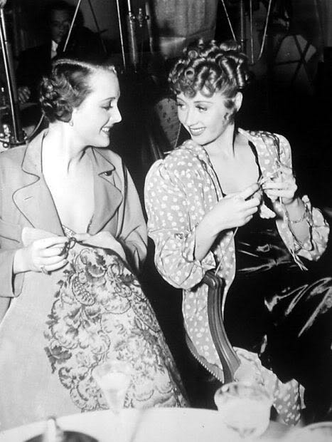 "Mary Astor stitches while Joan Blondell knits on the set of ""There's Always a Woman"", 1938."