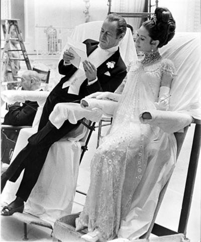 """Rex Harrison and Audrey Hepburn relax on their slant boards on the set of """"My Fair Lady."""""""