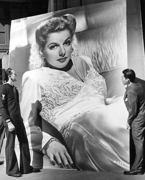 "An eight-feet by ten-feet picture of Ann Sheridan rests outside a Warner Bros. office in New York City before being sent to the soldiers of Little Norway, Canada. Sheridan plays a Norwegian freedom fighter in ""Edge of Darkness."" April, 1943."