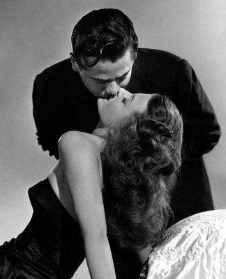 "Have you ever noticed that movie kisses are sometimes staged in such a manner that if done in real life would result in severe cramps if not a life time of orthopedic problems. Here's Glenn Ford improbably kissing Rita Hayworth in ""Gilda."""