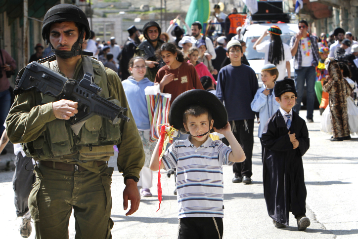 Jewish children wearing Purim costumes are guarded by Israel soldiers in the Jewish city of Hebron, currently under occupation by Arab Muslim colonials.