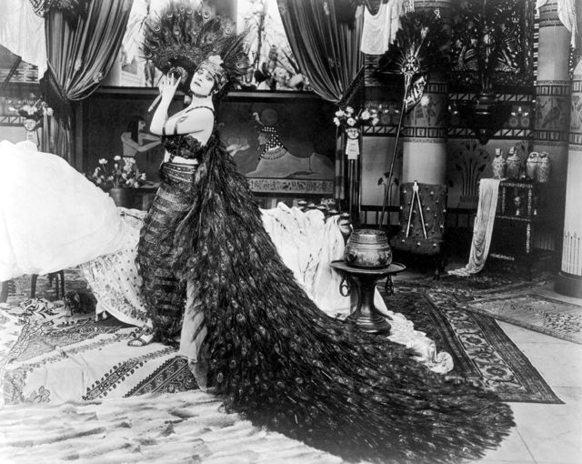 "Theda Bara, born Theodosia Goodman, holds a peacock feather in a still from ""Cleopatra"" (1917). Bara is wearing a costume consisting of a bustier and sarong with a long peacock feather train and headdress. Only ten seconds of this elaborate film have survived and we have no idea who designed the costumes but still photos testify to one ravishing costume after another."