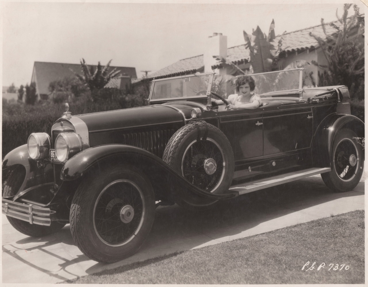 Clara Bow in a 1927 Cadillac Dual Cowl Phaeton in the driveway of her home at 512 N. Bedford Drive, Beverly Hills, CA.