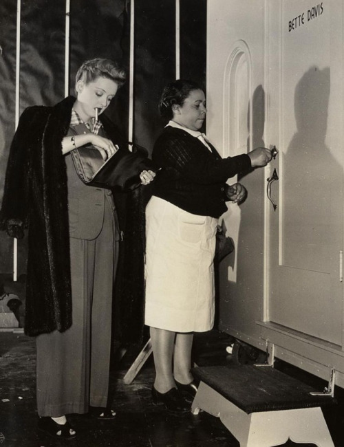 "Bette Davis with her maid Marie on the Warner Brothers lot, 1943. ""It has been my experience that one cannot, in any shape or form, depend on human relations for lasting reward. It is only work that truly satisfies. No one has ever understood the sweetness of my joy at the end of a good day's work. I guess I threw everything else down the drain. I will not retire while I've still got my legs and my make-up box."""