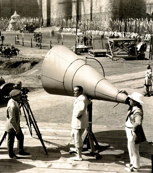 Douglas Fairbanks (center) with director Allan Dwan (right) on the set of Robin Hood (1922). Giant megaphones were used to direct large crowds of extras.