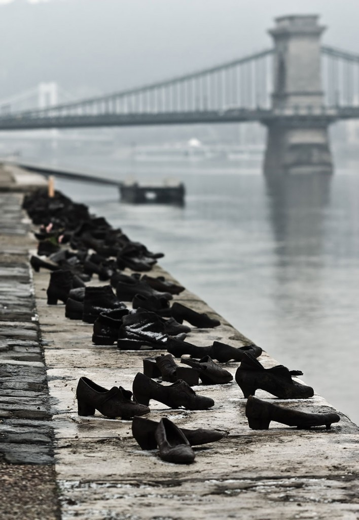 During WWII, Jews in Budapest were brought to the edge of the Danube, ordered to remove their shoes, and shot, falling into the water below. 60 pairs of iron shoes now line the river's bank, a ghostly memorial to the victims.  'Shoes on the Danube Promenade' by Can Togay and Gyula Pauer