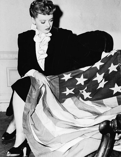 I haver no idea what's going on this photo of Bette Davis and the flag. But the very mystery of her expression give the pose a terrific theatricality.
