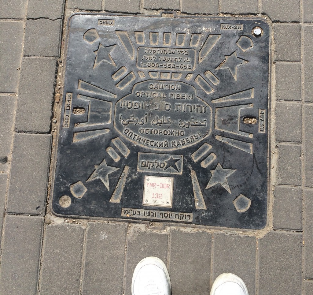 Multilingual manhole cover in Jerusalem: English, Hebrew, Arabic and Russian.
