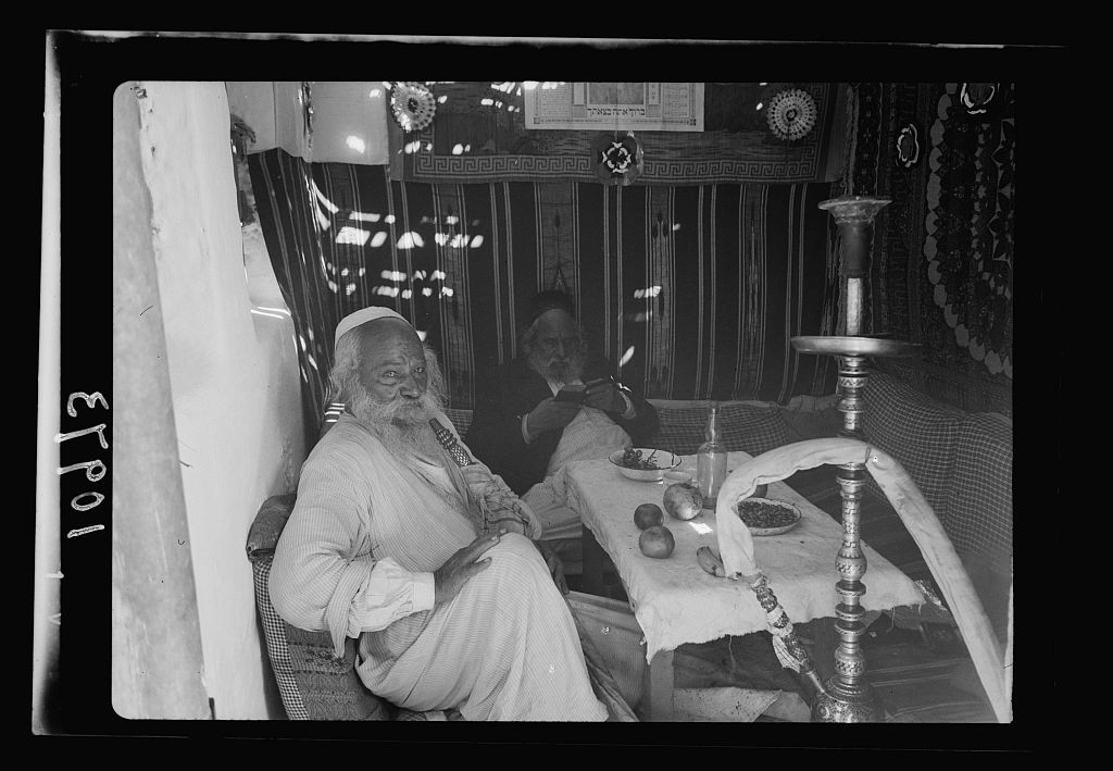 A Sephardi Jew named Avram relaxing in his Succah with a friend, 1939.