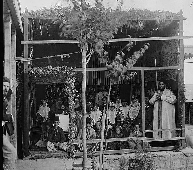 Bukharan family in their sukka (circa 1900). Note the man on the right holding the lulav and etrog.