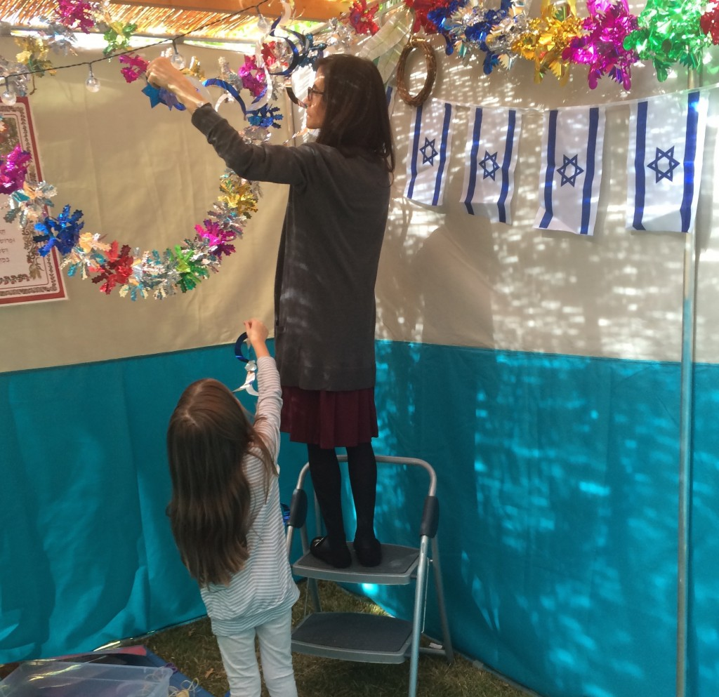 Maayan and Karen work together decorating the Sukkah.