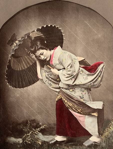 "Kusakabe Kimber, Geisha in the Rain, hand tinted albumen print. In addition, Kimbei here invents ingenious studio ""special effects"": he imitates the rain and the wind by directly striating the negative and by tensing the threads moving the material of the kimono of this Japanese woman, who is at the mercy of a reconstructed storm,1885."