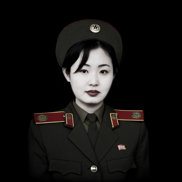 Éric Lafforgue, Miss Kim Miss Kim lives in Pyongyang, North Korea. She is wearing uniform but is not a soldier. She is the French-speaking guide at the 'Victorious Fatherland Liberation War Museum.'Kim, a young french military speaking guide at the Army Museum. Women may represent more than 10 percent of the entire North Korean People's Army. North Korea is the most militarised country in the world.According to the US State Department, North Korea has the 4th largest military in the world, at an estimated 1.2 million armed personnel for 23 millions north koreans. Even if many think NK has nuclear bomb, the guns, cars, military equipment seems to come from the 50's... The Korean People's Army is the military of North Korea. Kim Jong Il is the Supreme Commander of the Korean People's Army . The famous Bush's Axis of evil includes Iran, Iraq, and North Korea. In NK, every young man stay for 6 years in the Army. It means that for 6 years, he won't have many news from his families because there is no email, mobile and very few private phones in North Korea.