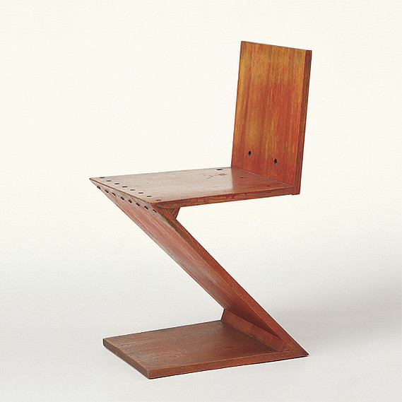 Zig Zag Chair Designed by Gerrit Thomas Rietveld Design: 1932-34 Production: 1935 to c.1955 Manufacturer: Metz & Co., Amsterdam Size: 75 x 37 x 44.5; seat height 42.5 cms Material: red-stained elm, brass screws
