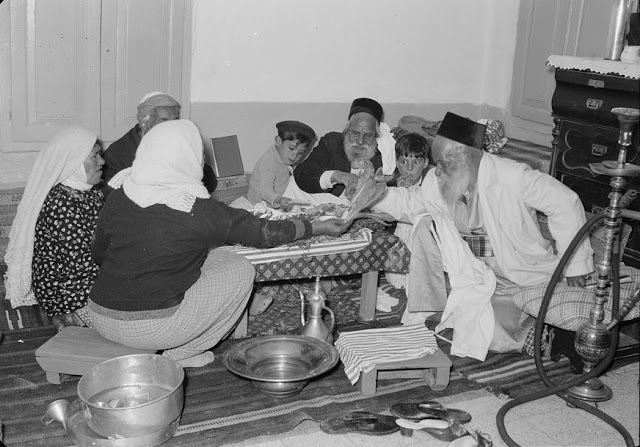 Yemenite Passover Seder in Jerusalem. Note that they are eating the bitter herbs, 1939.