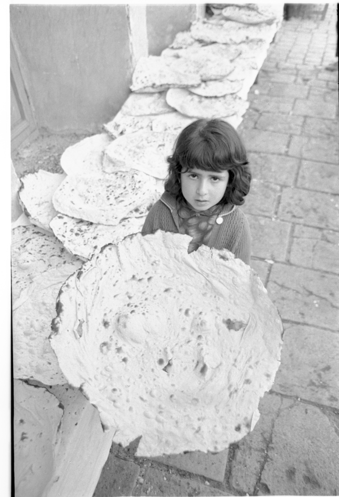 A young Jewish girl holds up a hand-baked matzah for the camera. Teheran, Iran, c 1964.
