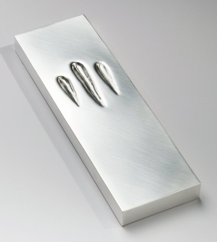 "Touching Mezuzah Sari Srulovitch, Israeli, b. 1964 Israel, 2002 Silver: hand-worked with repoussé 7 11/16 × 2 3/8 × 5/8 in. ""This mezuzah is indented like the well-worn steps of ancient buildings, as if to reflect the touch of thousands of hands that have reached up to kiss the mezuzah on the doorpost of Jewish homes for generations. The gentle indent on the clean, modern lines of this mezuzah beckons us to touch it. As we do so, we recall our heritage and the ancient command of the Lord to the Israelites in Egypt to mark the doorposts of their homes to protect them from the plague on Egypt's firstborn. The touch of the ages has left an indentation in the shape of the Hebrew letter shin, a traditional ornamentation on mezuzot symbolizing one of God's names. Part of the permanent collection at the Israel Museum, the Jewish Museum N.Y.and the Jewish Museum Berlin."""