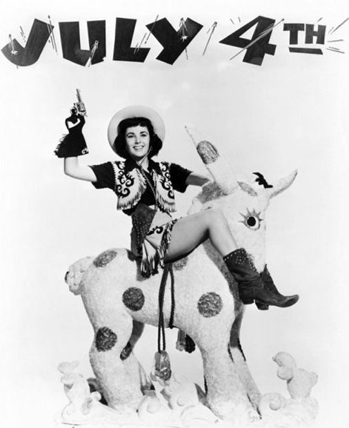 This July 4th photo seems to be referencing Taylor's classic role in National Velvet ('44). Unfortunately, the stuffed horse comes across as deeply strange.