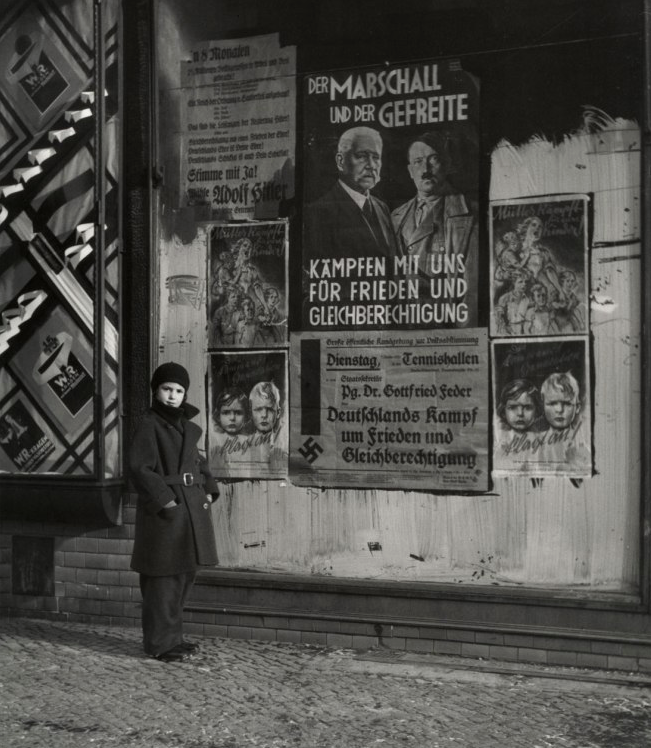 "Roman Vishniac Vishniac's Daughter Mara in Front of an Election Poster for Hindenburg and Hitler that reads ""The Marshal and the Corporal: Fight with Us for Peace and Equal Rights,"" Wilmersdorf, Berlin, 1933 ""Fight with Us for Peace and Equal Rights"" This sounds like the Democrat party whose obsession with equality is, in essence, the road to fascism."