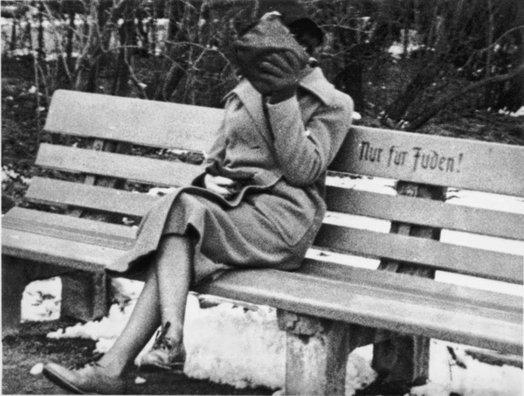 """A jewish Woman conceals her face as she sits on a park bench marked """"Only for Jews,"""" Austria, 1938"""