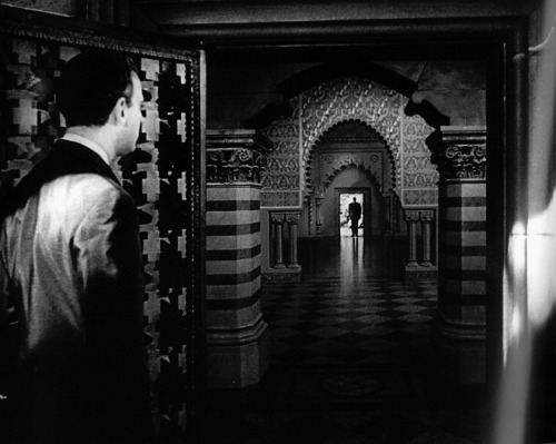 Above: The partial set from Citizen Kane consists of a foreground doorway and the butler (Paul Stewart), while Kane (Orson Welles) stands on a distant soundstage floor. Below: The final, deep-focus image was completed with a matte painting by Chesley Bonestell. The live-action elements of the doorway in the foreground and Kane in the background were optically composited with a painted hallway, columns, and floor. The distant reflection of Kane on the floor was painted as well. Source: The Invisible Art
