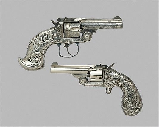 Smith and Wesson .32 Single-Action Revolver, 1889–90. The grip is sheathed in silver and etched with foliage around shaped panels inlaid with laminated metal that has a wood-grain pattern. This Japanese technique, called mokume, was one of various metalworking forms explored by Tiffany and Company's chief designer, Edward C. Moore. His experimentation with Japanese design elements and media helped to establish Tiffany's international reputation in the 1870s. Source: Metropolitan Museum of Art, NY